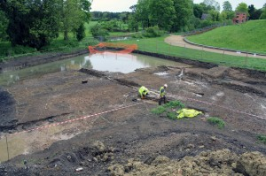 Archaeologists excavating the series of post holes and ditches in Area 1. The portion under water marks the location of the vast defensive ditch.