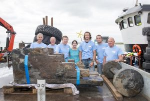 A group of people standing behind freshly excavated gun carriage from the London