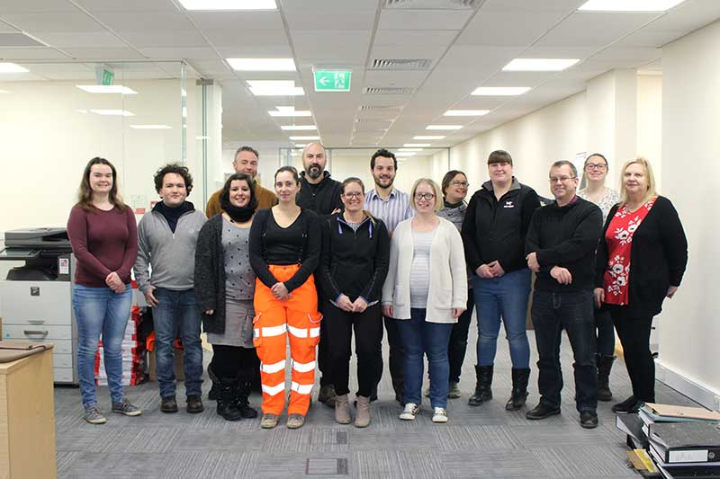 a group of people (MK team) standing in the new office