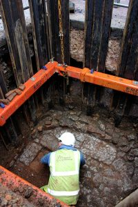 a person in a hardhat excavating an inspection chamber
