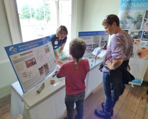 archaeologist behind the table showcasing artefacts. A woman and a boy in front of the table asking questions and looking at the finds