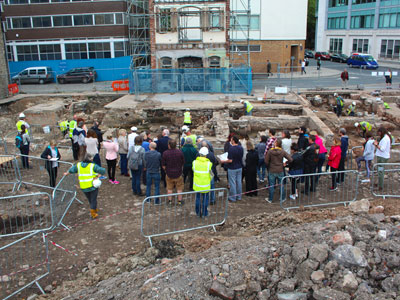banner for Talks and events link-a group of people standing in the middle of excavation area