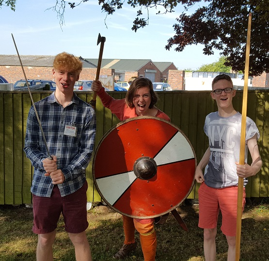 three people standing in front of the camera with weapon, woman in the middle holding a shield and an axe looking scary