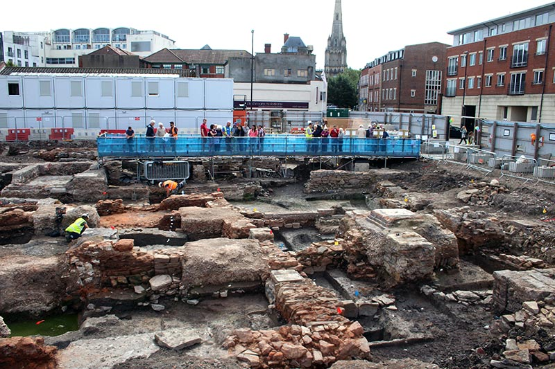 view of the visitor's bridge with people looking at the excavation area