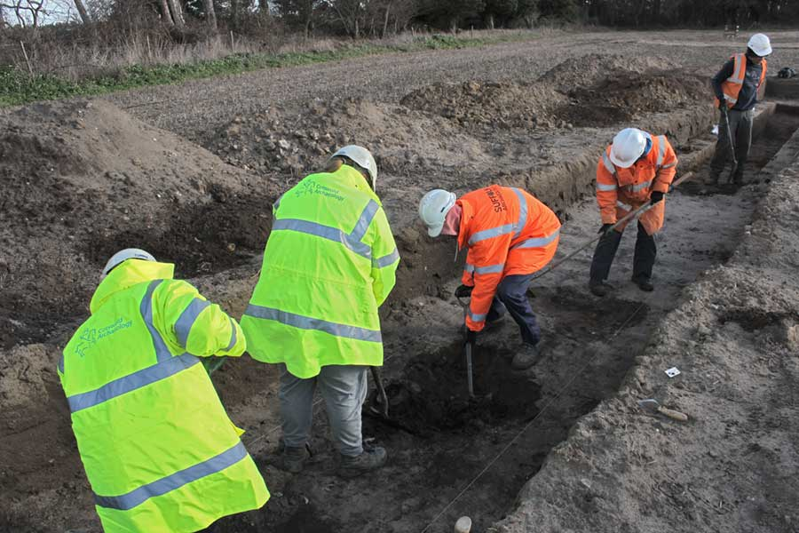 four people in a trench digging together, two wearing CA PPE and two in Suffolk archaeology brand clothes