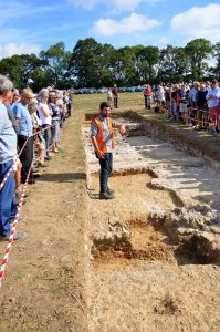 an archaeologist showing the excavation site to a crowd of people