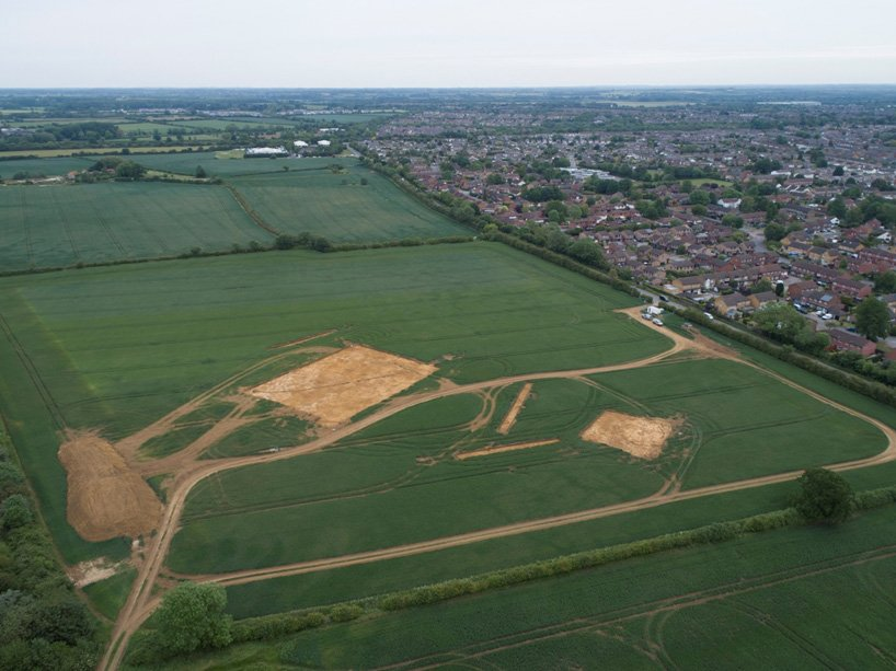 Two of the areas of excavation at Howes Lane on the western side of Bicester, looking north-east. An Iron Age roundhouse is just visible in the smaller area, with Iron Age enclosure ditches in the larger area