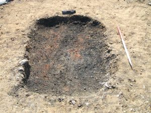 One of the burnt pits from Eye after the flints have been removed and showing the base layer of charcoal and in situ burning
