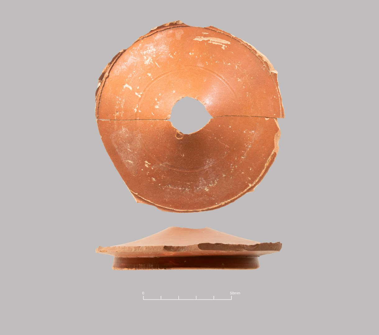 Central Gaulish Samian ware dish from cremation burial. Base has been deliberately perforated before burial. Middle Roman (c. 150-200 AD)