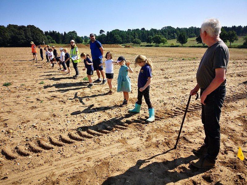 Children from Redlesham Primary School fieldwalkinf with Professor Tom Williamson Ⓒ Suffolk County Council